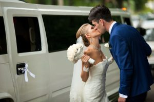 Brunette groom kisses a tiny bride standing before a Rich limousine